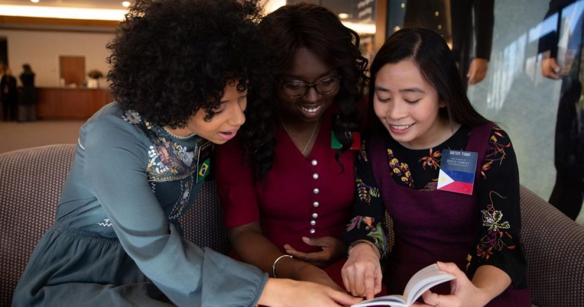 Sister missionaries excitedly peruse the new handbook | Intellectual Reserve